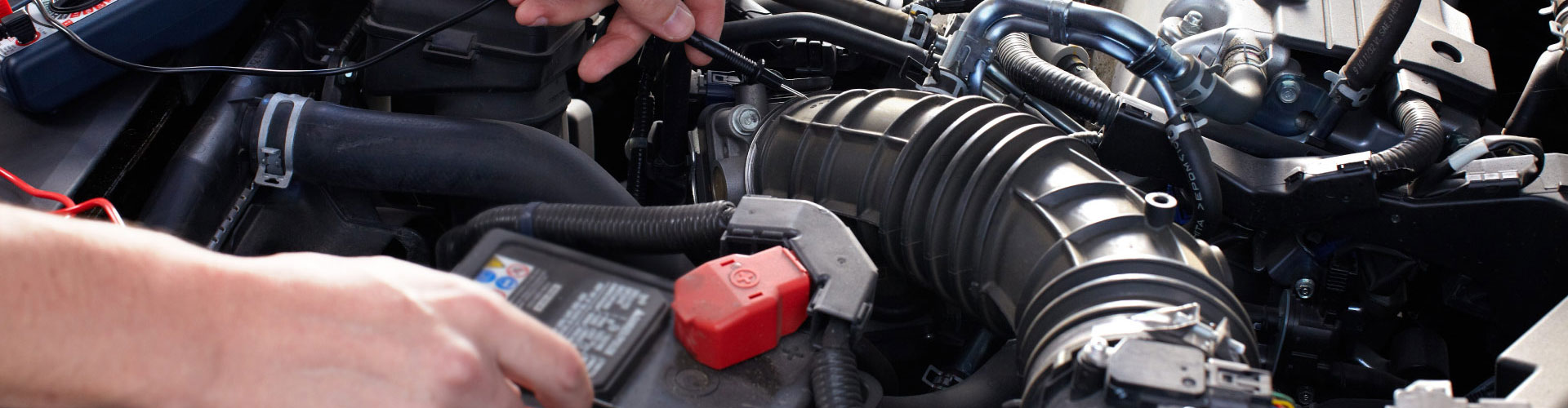 An auto mechanic checking a car engine